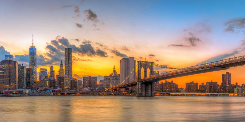 Brooklyn bridge and downtown New York City in beautiful sunset.